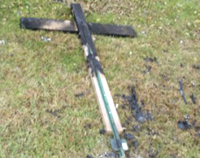 This undated file photo provided by Gary and Alina Grewal of Hardwick Township, N.J., shows a charred cross that had been burned on the lawn of their home. The Grewals placed a banner congratulating President-elect Barack Obama on his election victory in their yard and found the banner wrapped around the charred cross Nov. 6, 2008. (AP / Courtesy of Grewal family)