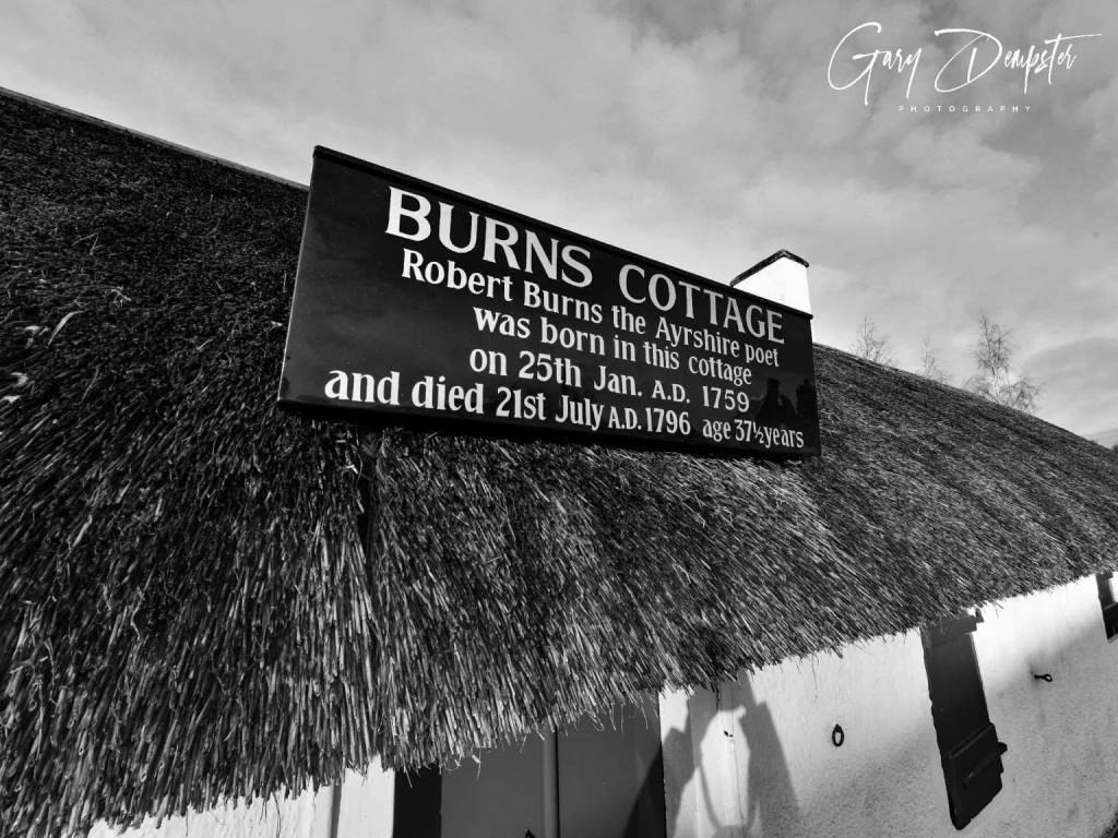 Thatched roof with a dark sign with gold lettering Burns Cottage Robert Burns the Ayrshire poet was born in this cottage 25 January AD 1759 and died 21 July AD 1796 age 37 and a half years