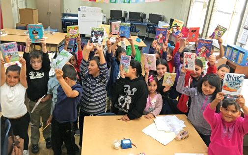 Photo courtesy Carrie Benuska Second-graders across Pasadena Unified School District hold up books they received through the recent local Realtors book drive initiative.
