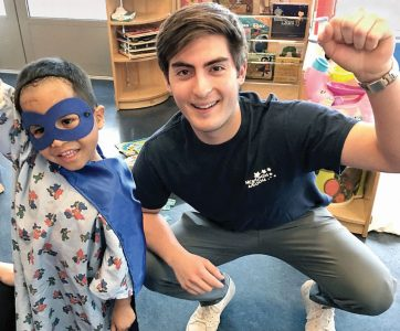 Photo courtesy Once Upon a Room A young patient shows off his superhero skills beside Thomas Gonzalez, a Pasadena resident who serves as Junior Room Crew treasurer, during one of the group's recent room-decorating events.