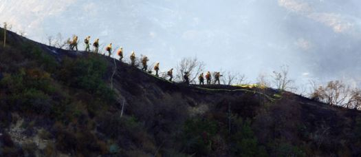 A team of firefighters lines a ridge in the San Gabriel Mountains.
