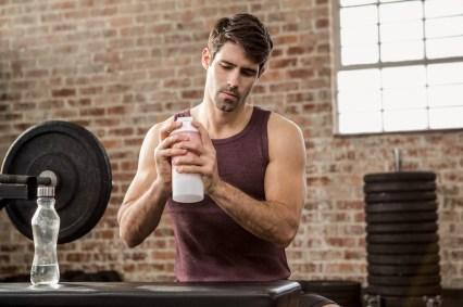 Man shaking shaker bottle at the gym