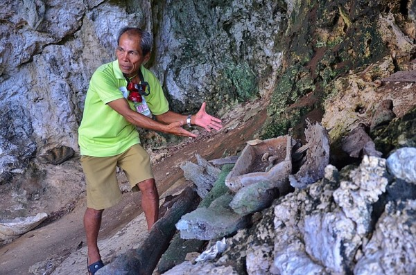 Tour Guide showing some wooden boat coffins discovered in one of the caves
