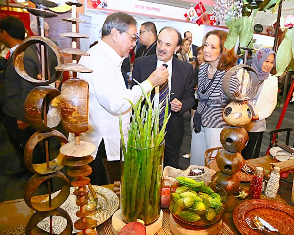 At the MFM 2016 Trade Exhibition. Tourism Secretary Ramon R. Jimenez, Jr. showing a local produce to Spanish Secretary of State for International Cooperation Jesus Gracia, while Lourdes Plana of Foro de Debate looks on.