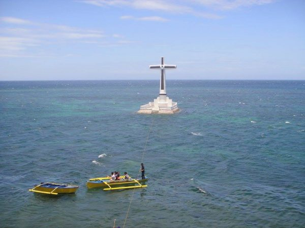 Tour of Camiguin - Small boats cruising towards the landmark cross above the Sunken Cemetery for a closer look
