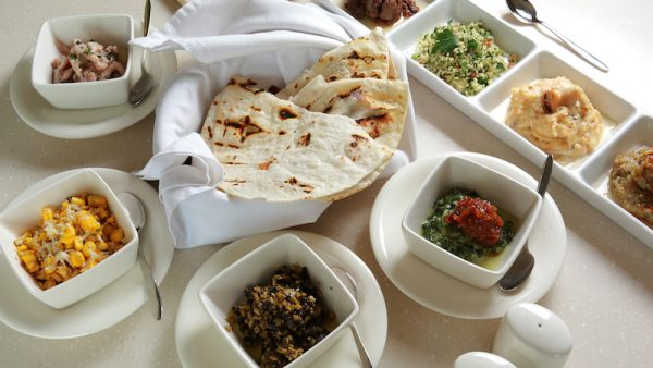 A Mediterranean ensemble of dips including couscous with coriander and a dip with red bell pepper