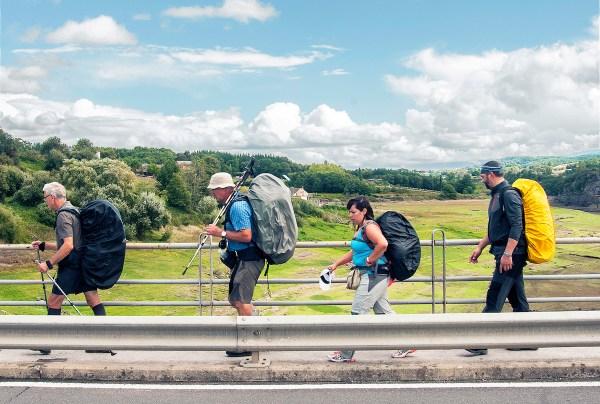 Four peregrinos cross the bridge single file.