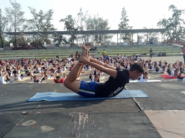 Jervy, a yoga instructor, shows the boat position or navasana.