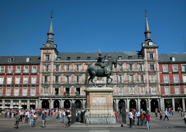 The bronze stature of King Felipe III stands in the middle of bustling Plaza Mayor with beautiful reliefs on the facade of its colonnaded buildings.