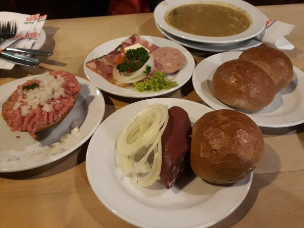 From clockwise, top: pea soup, bread rolls, black pudding sausage, Mett, and liverwurst with brawn Mett.