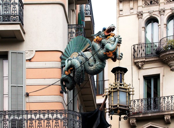 An art deco sculpture of a Chinese dragon holding a lantern with an umbrella.