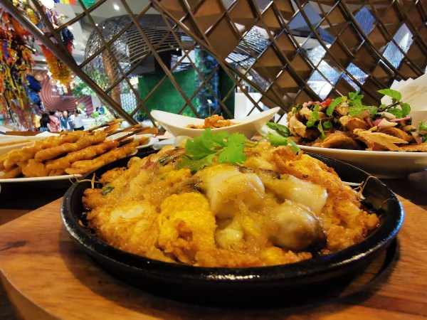 Sizzling seafood with eggs in hot plate