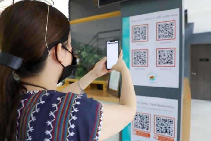 Tourism Secretary Puyat scans a Quick Response (QR) code for check-in procedures as tourism establishments adapt to digitalization and new normal