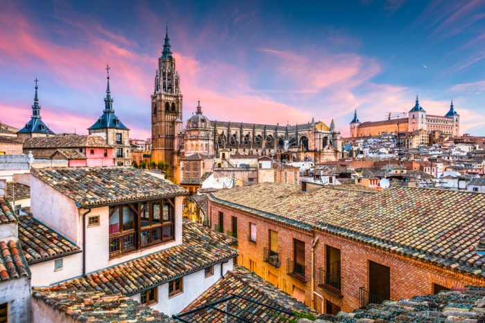 Toledo, Spain cathedral and rooftops at dawn via Depositphotos