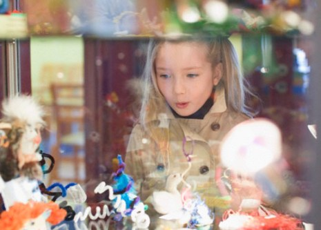 Girl window shopping outside toy store