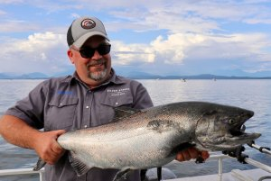 Man in hat holds king salmon near Campbell River, BC