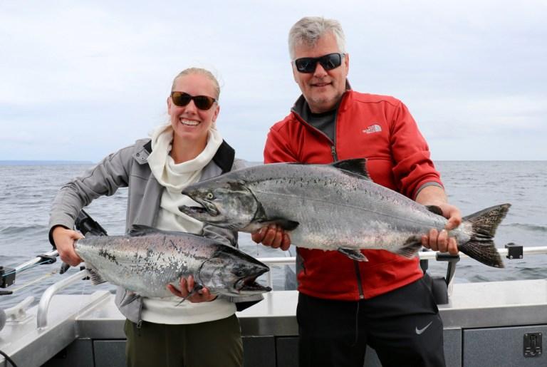 man and woman with big spring king salmon fishing