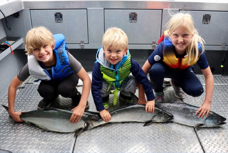 three blond children hold chinook salmon