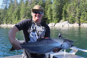 man in hat and sunglasses with chinook salmon