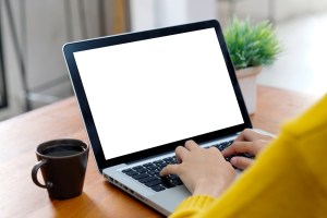 Woman typing on a laptop with a wooden desk and a cup of coffee. You can get Online therapy in California telehealth from a skilled provider from Outside the Norm Counseling in Temecula, CA