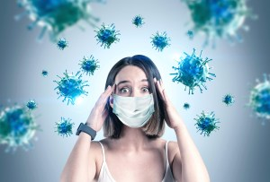 Woman wearing a surgical mask holding her head while germs look like they are intensely attacking her due to Health anxiety about coronavirus pandemic needs online counseling in California from Outside the Norm Counseling in Temecula, CA