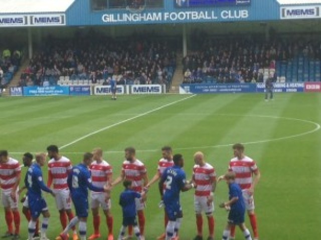 Gillingham (blue) shake hands with Doncaster Rovers