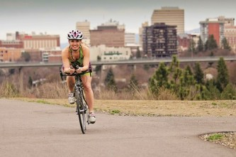 Woman cycling on the Spokane Centennial Trail with view of downtown Spokane in the background.