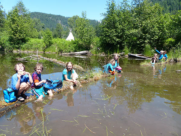 Twin Eagles Wilderness School summer campers wearing shorts with their legs in the murky waters of the shallow area of a lake, surrounded by trees with a view of hills in the far background.