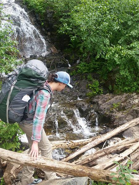 Photo of hiker traversing log jam.