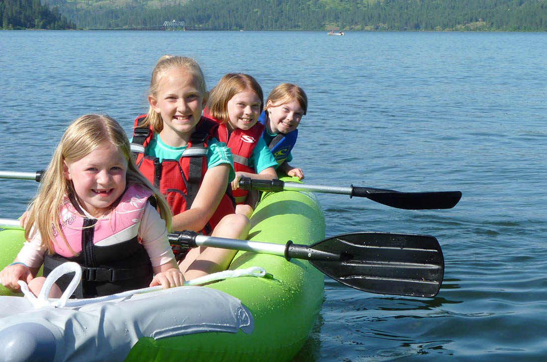 Photo of four kids in a kayak paddling on Lake Chatcolet in North Idaho.