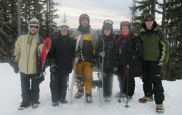 Photo of the Heston family posed on ski hill with skis and snowboards.