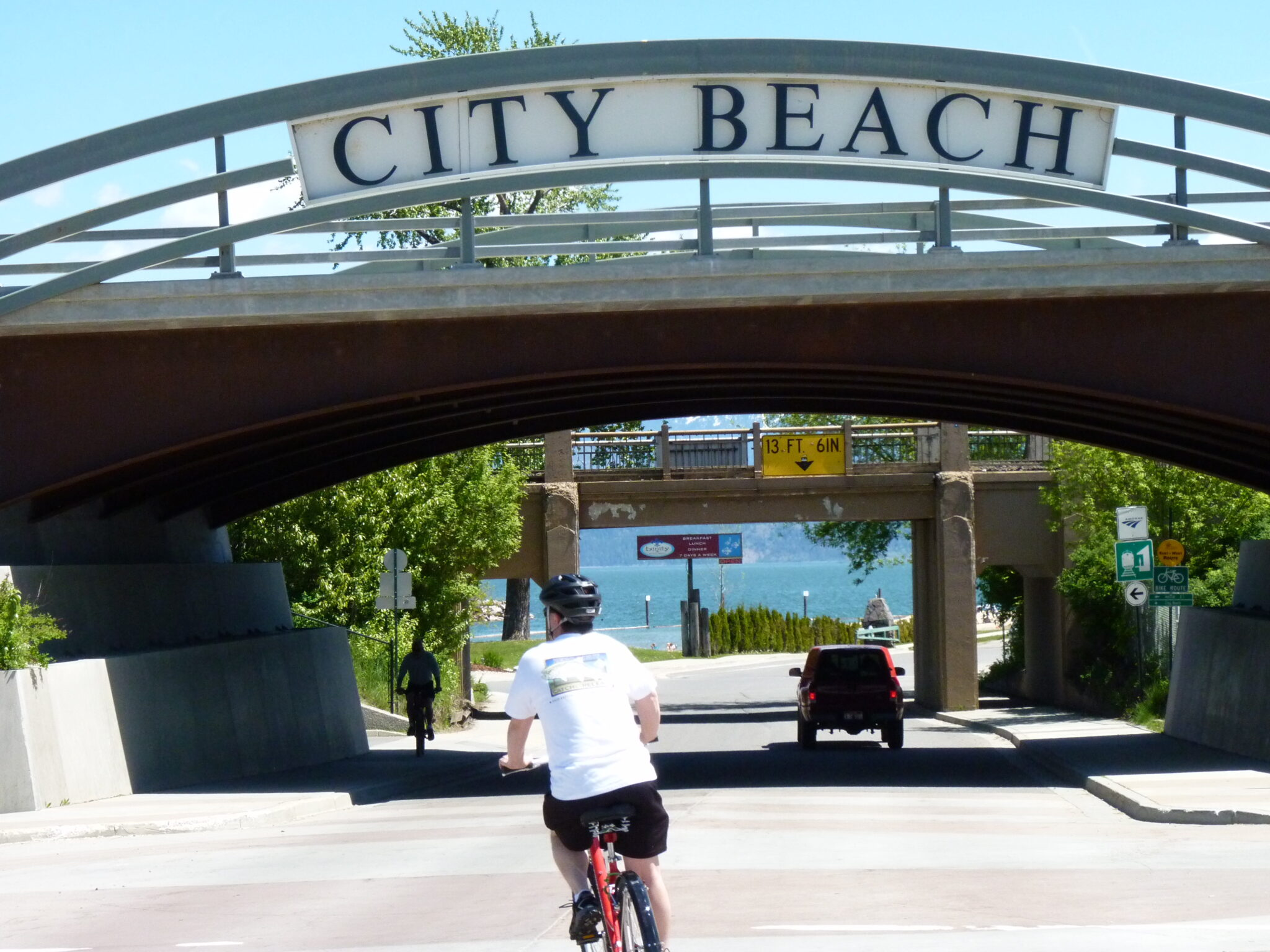 Man biking to City Beach in Sandpoint, approaching a big overhead sign at the park entrance.