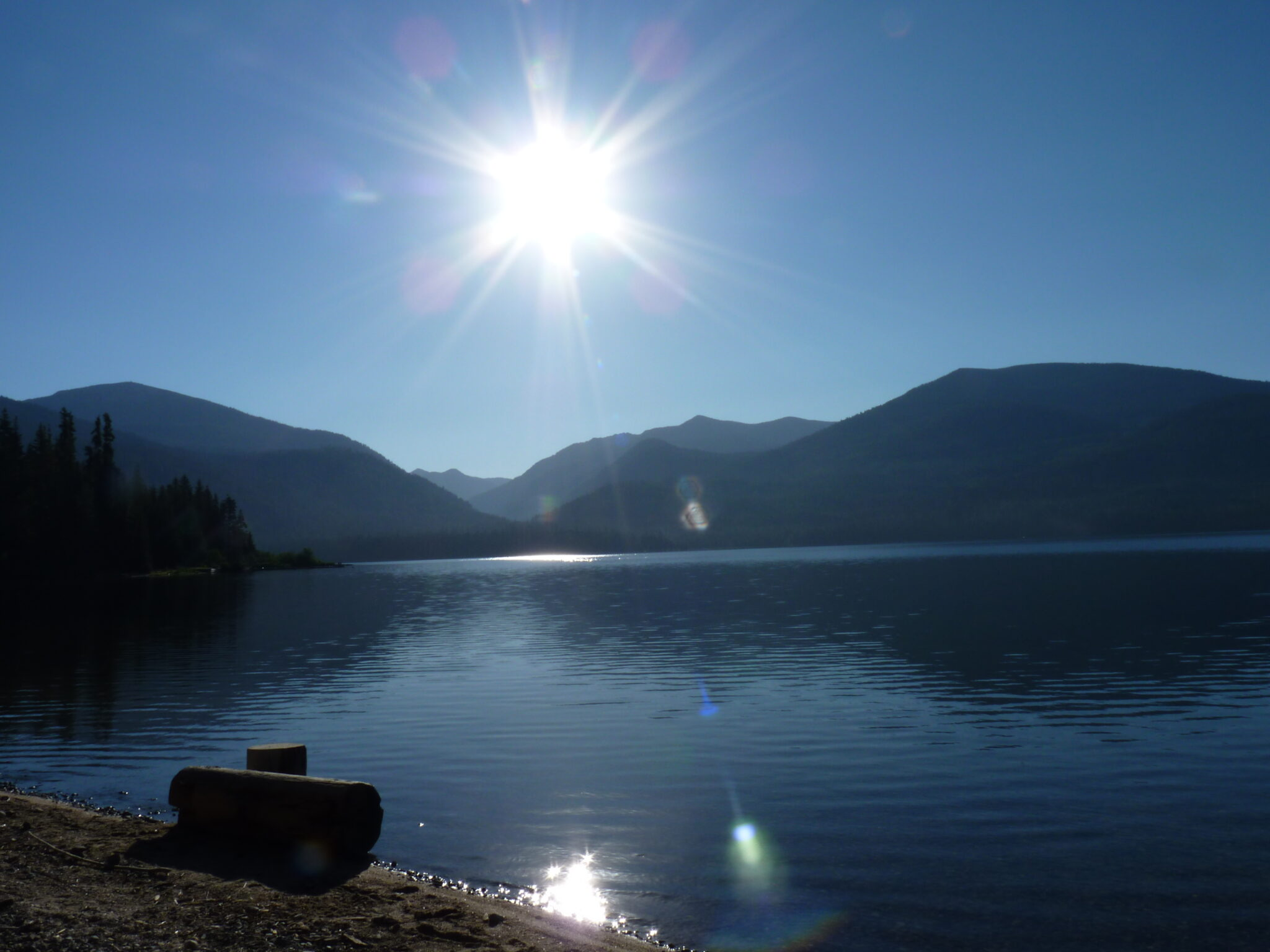 Still water of Priest Lake with mountain peaks and sun in the background.