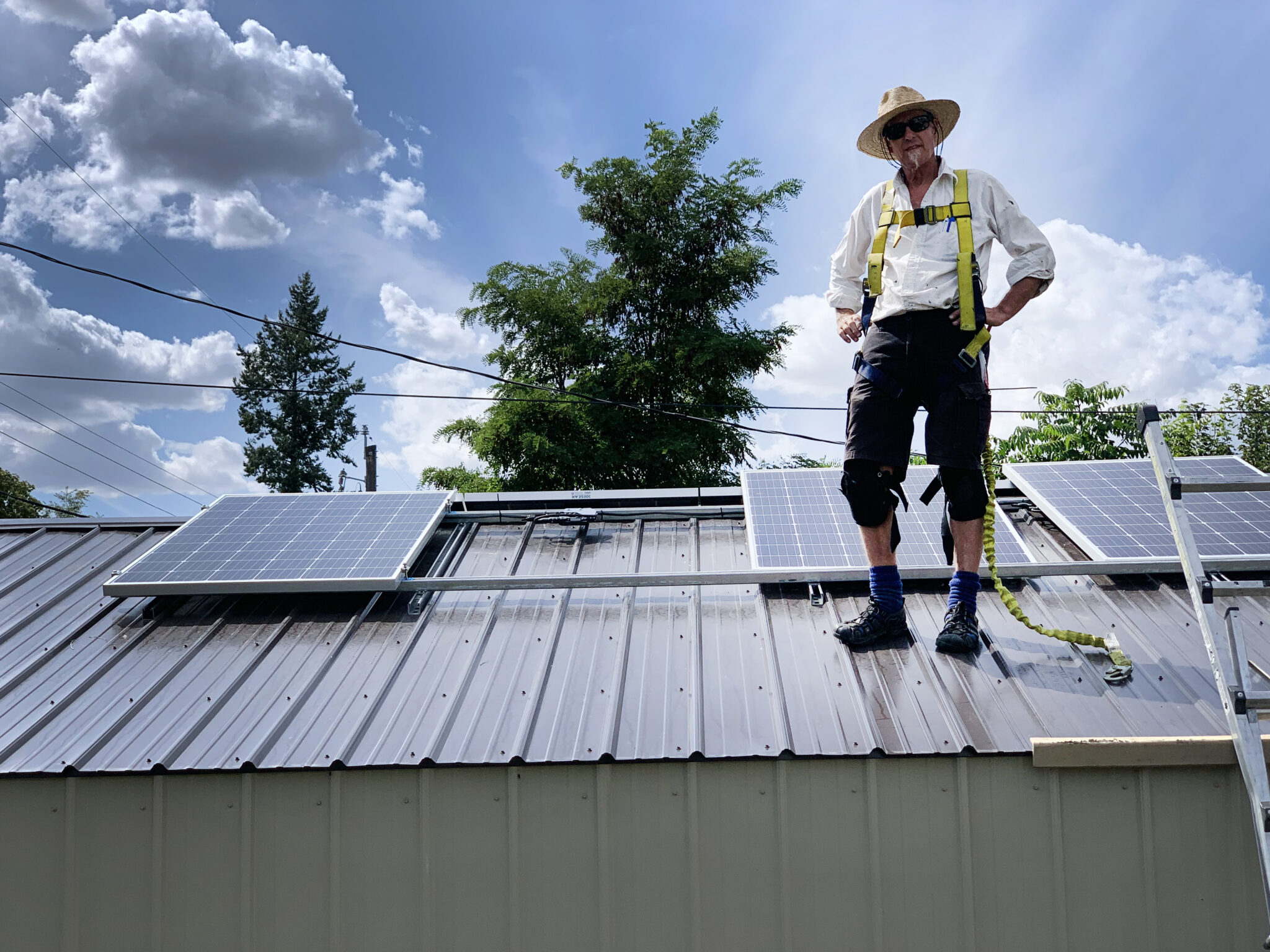 Eco Depot owner and solar installer standing on a roof with solar panels.