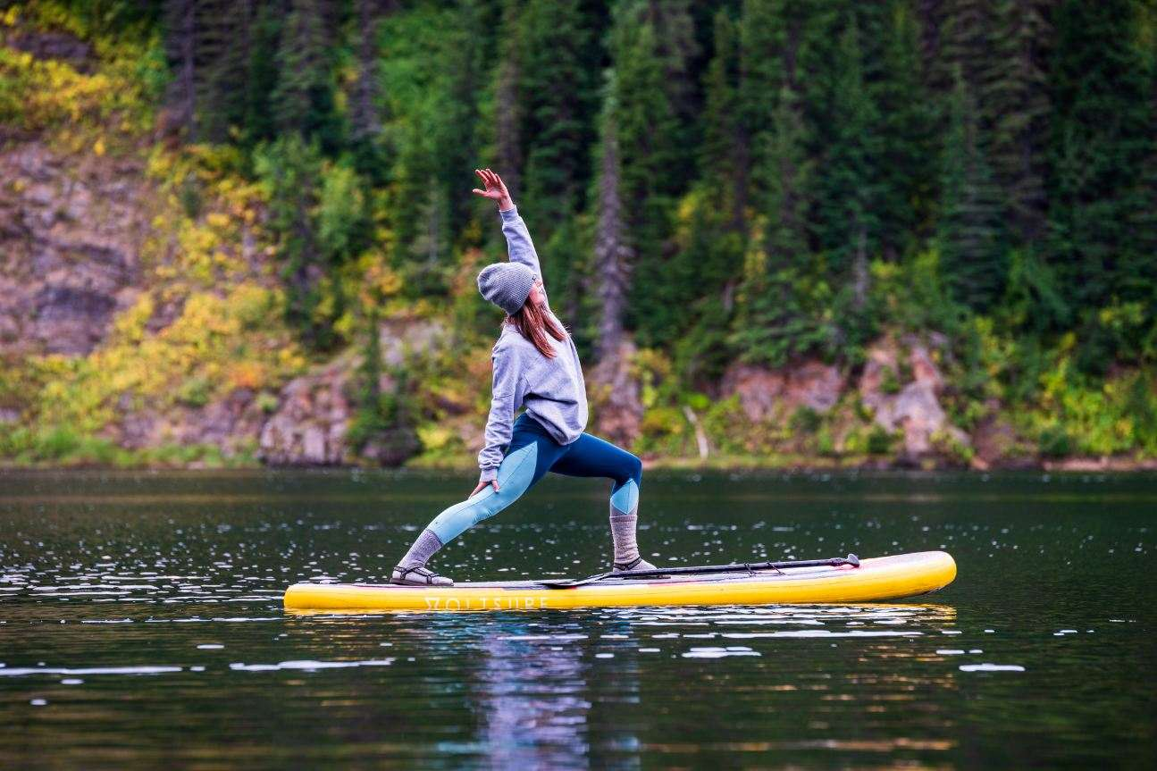A woman doing yoga while on a paddle board.