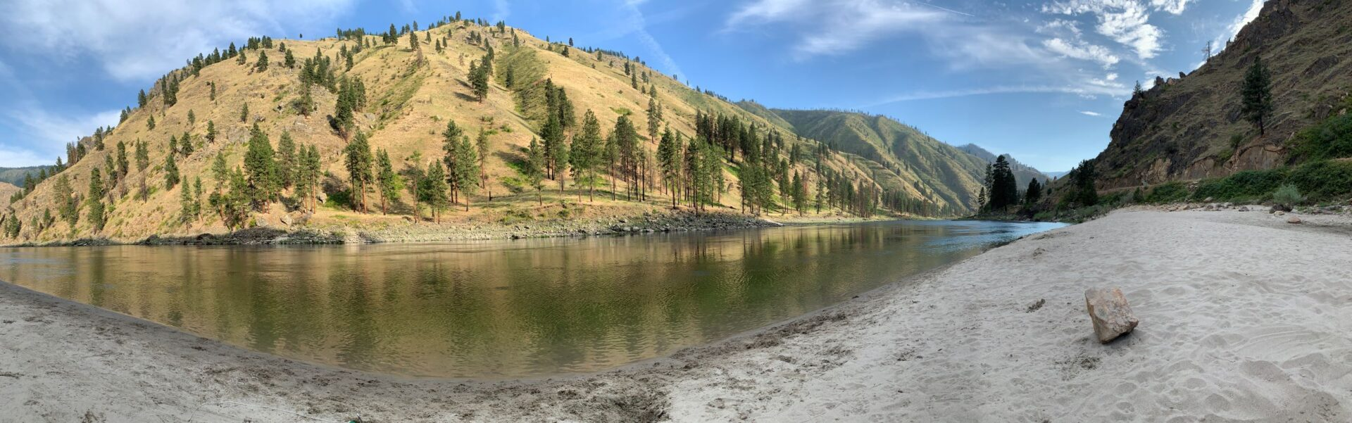 Sandy beach along the Snake River in Idaho. Rugged, hilly, arid landscape, and flat water of a river eddy.
