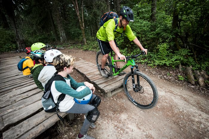 Man demonstrating mountain biking skills on a dirt trail to a group of students seated nearby on a wooden bench.