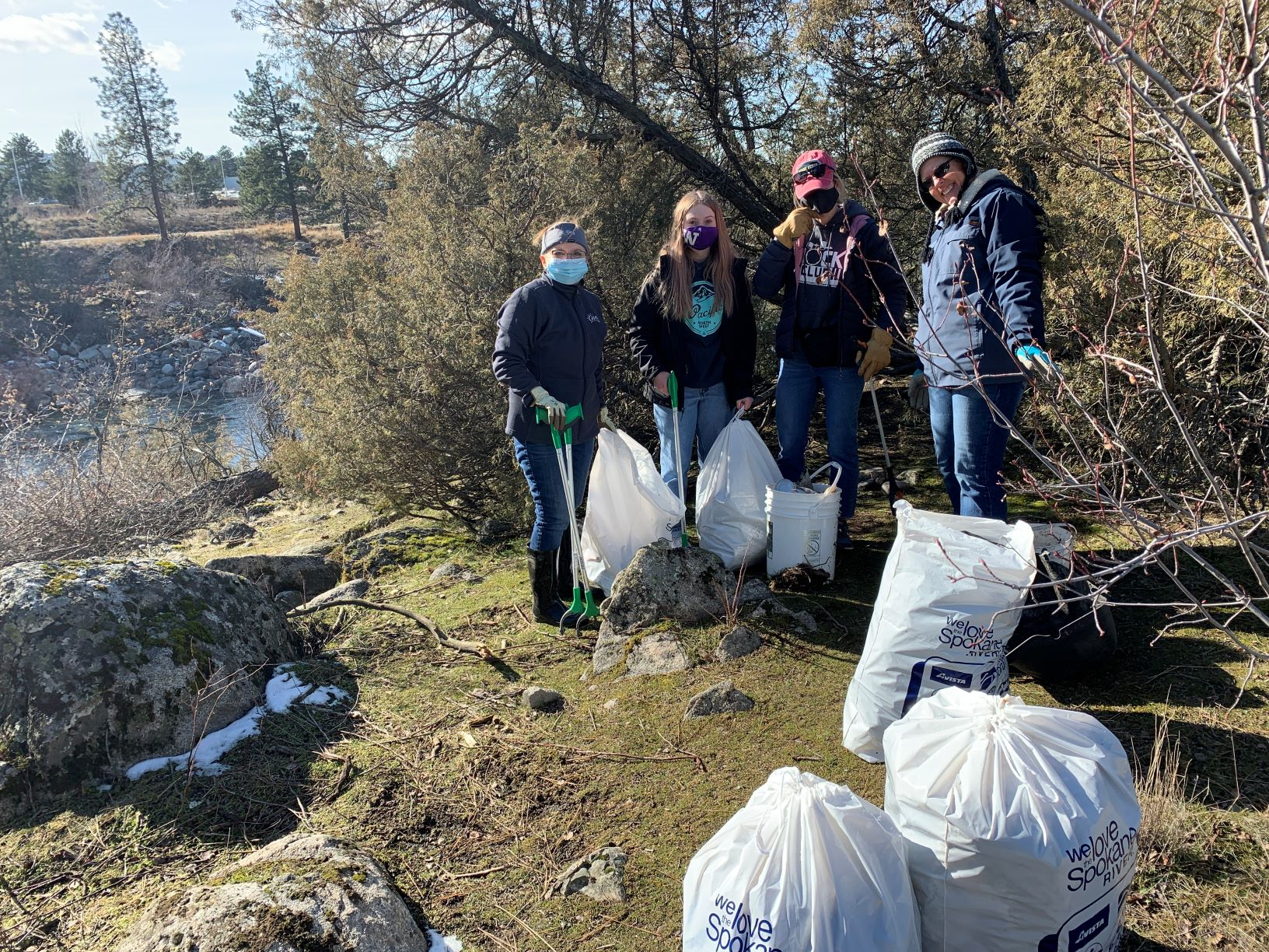 Four people volunteering during the Spokane River Clean-Up, wearing and holding pick-up pocking tools, and standing next to a large white bucket and four large plastic bags filled with collected trash.