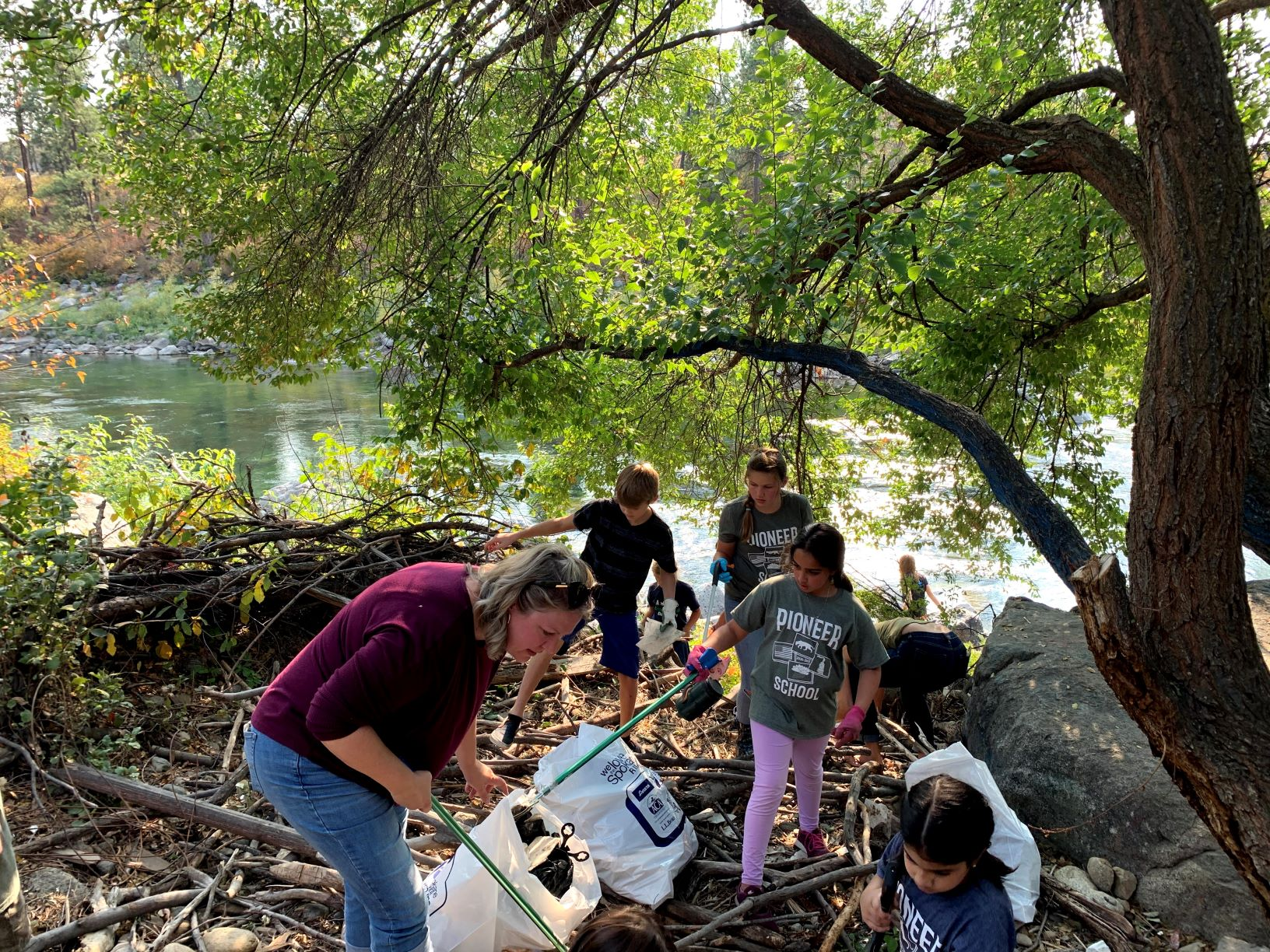 Volunteers, adults and youth wearing Pioneer School t-shirts, pick up garbage wearing gloves and using pick-up tools along the bank of the Spokane River.