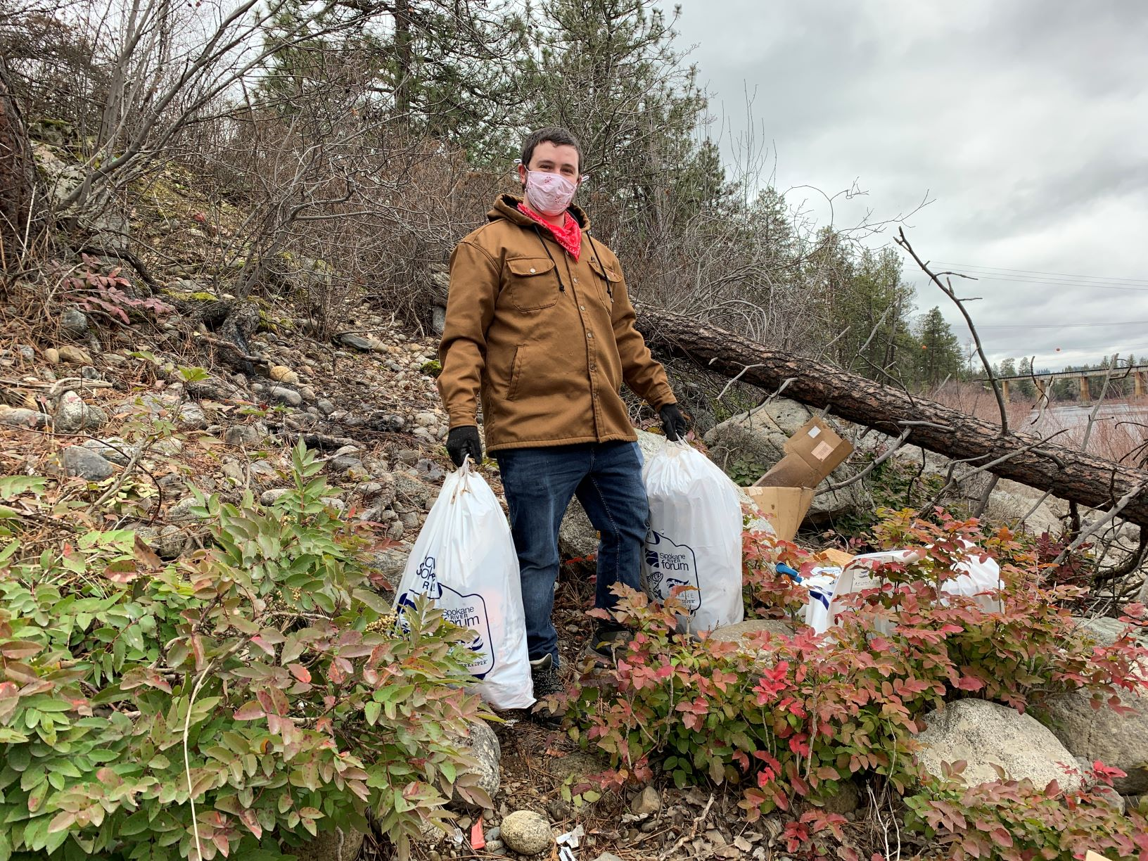 Man wearing a Carhart jacket, jeans, gloves, and facemask, carring two white plastic bags of litter and trash found along banks of the Spokane River.