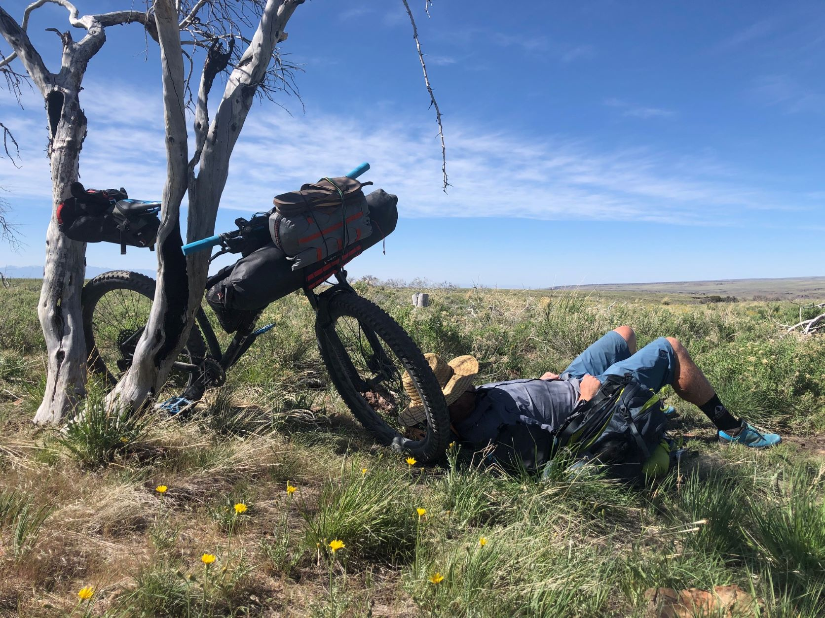 Man napping in the shade, leaning against his bike, in the remote landscape of southeast Oregon.
