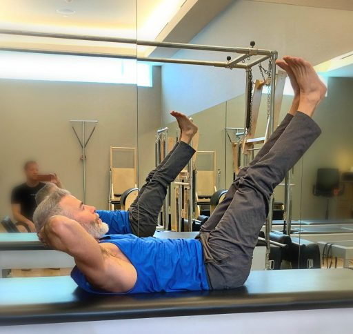 mature male athlete demonstrates mat exercises that require no equipment