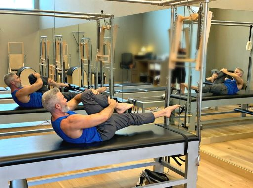 mature male athlete demonstrates a pilates mat exercise that does not require exercise or a gym membership