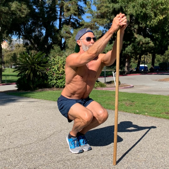 Male athlete uses pole to assist in doing narrow squats for ankle mobility.