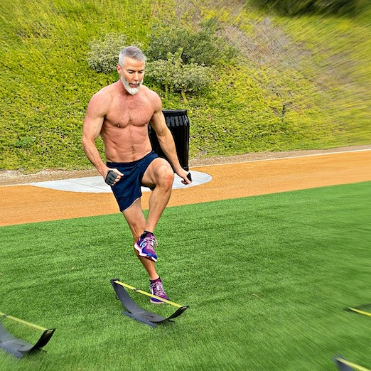 Mature male athlete doing hurdle speed drills at the park on Leg Day.