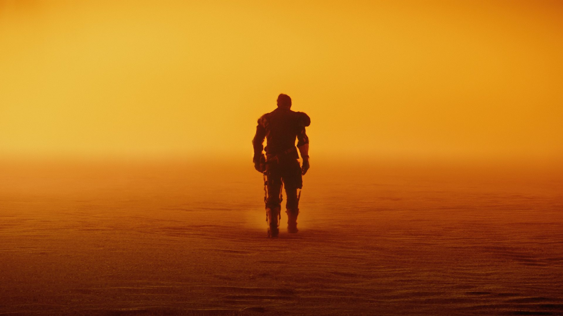Mad Max protagonist walking in the desert alone.