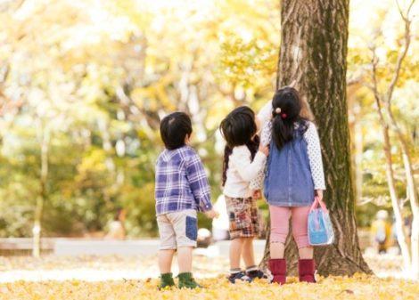 three children beside the tree