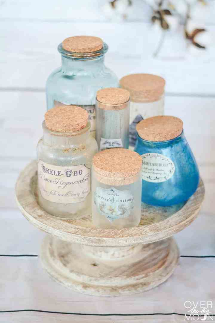 Distressed bottles with Harry Potter potion labels attached to the front on a cake stand.