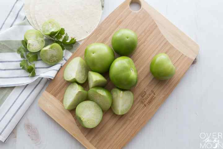 Cut tomatillos on a wooden chopping board.
