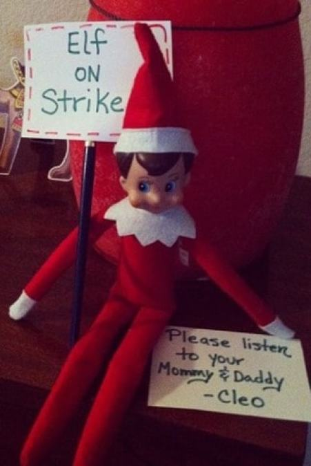 "An elf sitting on a table with a sign that says Elf on Strike. Then next to the elf, there's a note that ays ""Please listen to your Mommy & Daddy - Cleo"""
